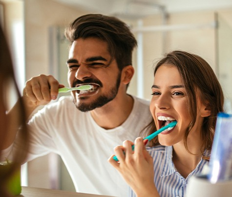 Man and woman brushing teeth together to prevent dental emergencies