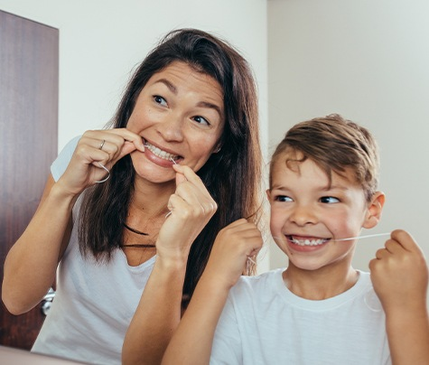 Mother and son flossing teeth together